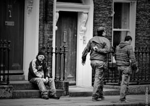 Fotografía de señor sentado en escalones, viendo pasar la vida