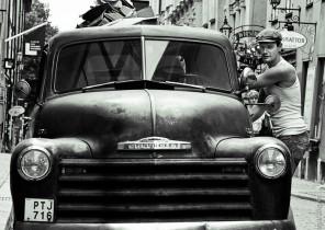Fotografía con look vintage de una furgoneta cargada con mudanza con conductor a la derecha
